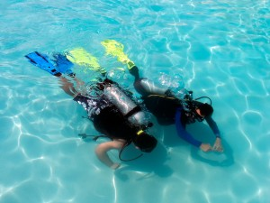 A boy taking scuba diving lessons in the caribbean resort.